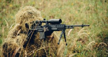sniper in camouflage suit looking at the target